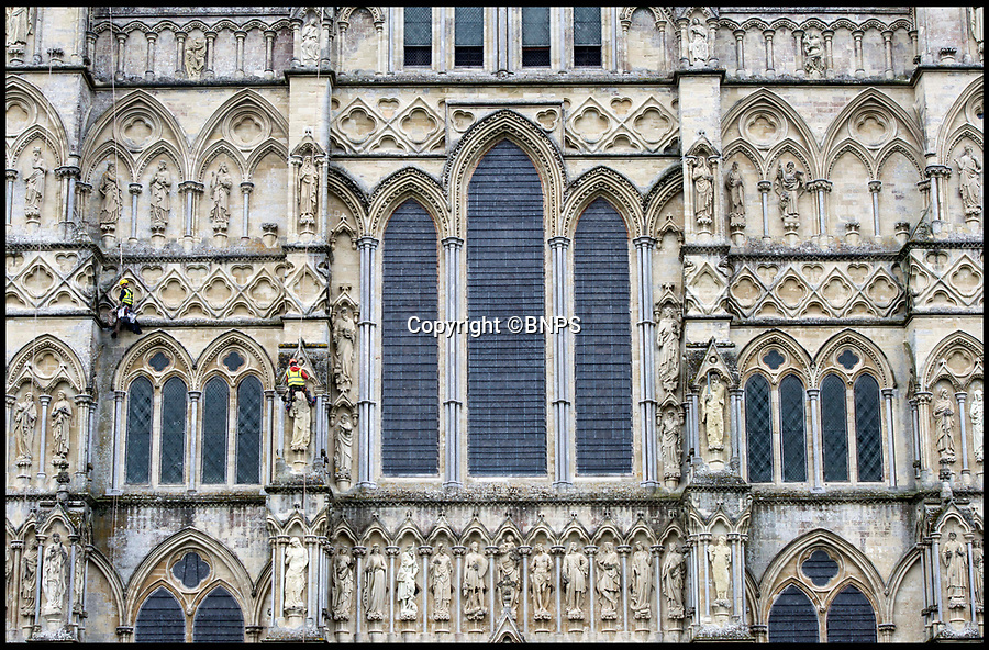 BNPS.co.uk (01202 558833)Pic: LeeMcLean/BNPS<br /> <br /> Salisbury Cathedral - Conservation on the west side of the Cathedral<br /> <br /> Specialist conservationists have been roped into dangling 80ft in the air to carry out important maintenance work at Salisbury Cathedral.<br /> <br /> Four rope access specialists from Vitruvius Conservation are working on the West Front of the historic building in Wiltshire over a three-week period.<br /> <br /> The hair-raising method may look more dangerous than scaffolding but it is actually completely safe and saves the cathedral authorities a small fortune.<br /> <br /> With westerly winds, the West Front gets the brunt of the bad weather causing erosion and it has 80 statues which need to be checked for loose stonework and damage.<br /> <br /> The team abseil down from the gables and carry out work repointing and pinning any loose stone while suspended on the ropes.