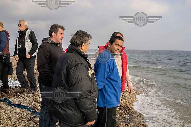 A group of local men watch as a boat carrying refugees lands on the shore. As soon as the boat lands the men will strip the boat of anything that can be recycled and sold on. Particuarly the fuel, the engine, rope and timber.