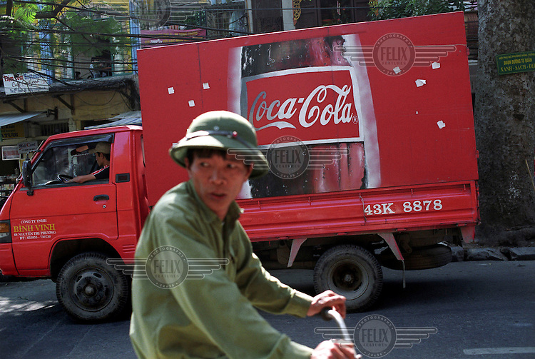 Coca Cola truck passing man on bicycle.