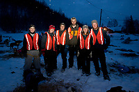 Dog handlers pose for a group photo at Takotna checkpoint during Iditarod 2009