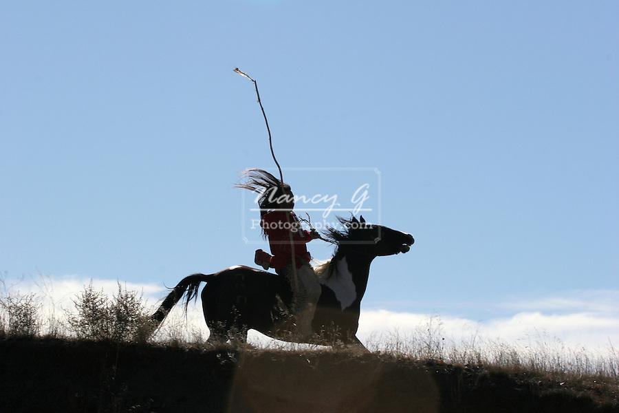 A Native American Indian man silhouetted riding horseback looking for ememies through the prairie of South Dakota