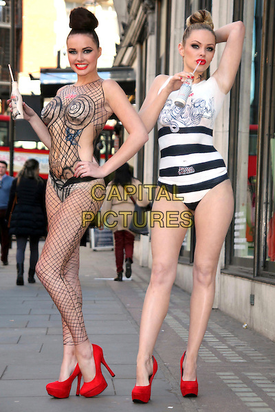 JPG Models.JPG & Diet Coke - photocall at Harvey Nichols, Knightsbridge, London, England..Two models pose for photos as award-winning body artist Carolyn Roper paints them as Diet Coke bottles, recreating Jean Paul Gaultier's latest 'Night & Day' designs for the brand..April 16th, 2012.full length posing black naked nude skin hand on hip hair up white striped stripes shoes fishnet bottle drink beverage red.CAP/JEZ  .©Jez/Capital Pictures.