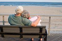 Retired senior couple relaxing on boardwalk bench