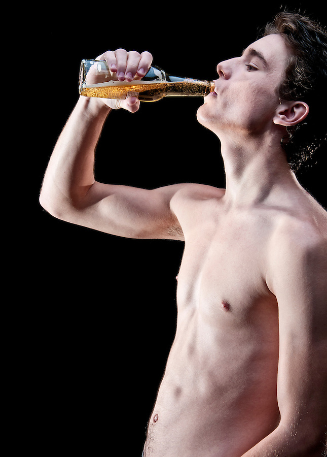 Young man drinking beer from a bottle, standing shirtless.