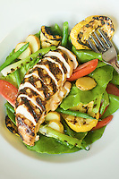 Grilled chicken breast on a bed of salad comprised of Spinach, Squash, Tomato, Leeks, and Potatoes
