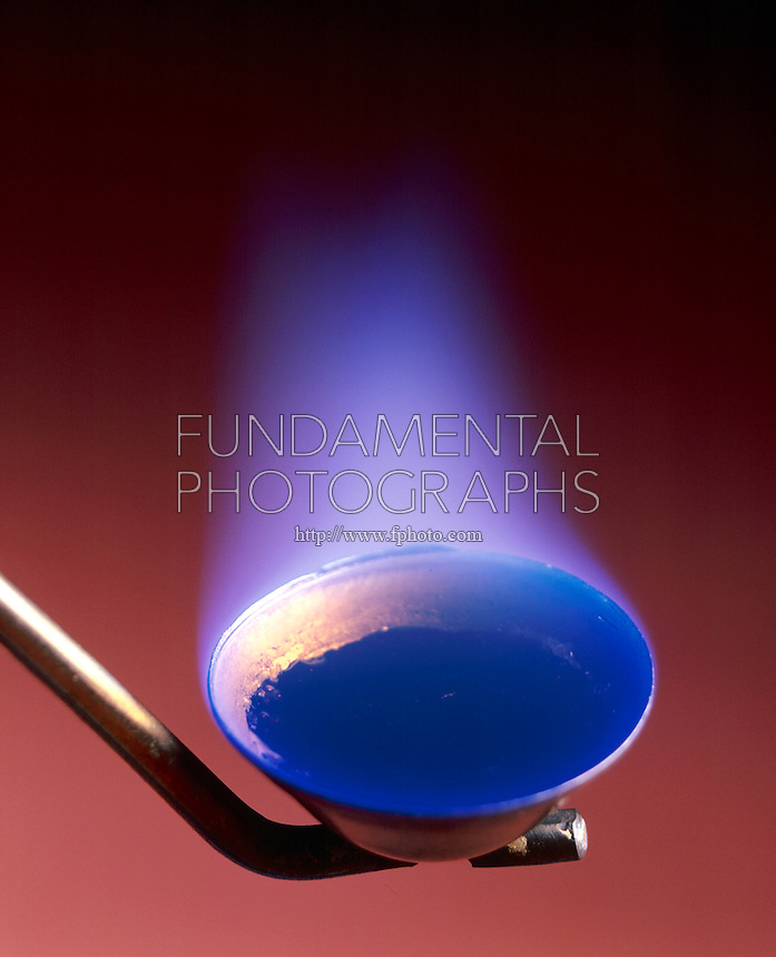 SULFUR BURNING IN AIR (3 of 3)<br /> Lump Sulfur In Deflagration Spoon<br /> Orthorhombic lump sulfur ignites in air above 261 degC with a blue flame to form sulfur dioxide gas (SO2).  SO2 is slowly oxidized in the atmosphere to form SO3 which dissolves in rainwater to give sulfuric acid or acid rain.