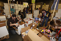 "Friday, February 15, 2013.   Volunteers Garrett Egeberg and Cheryl Zachary sort and pack an assortment of ""people food"" to be sent out to the 22 checkpoints along the Iditarod trail at Airland Transport in Anchorage."