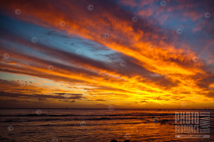 Colorful clouds streak across the sky above a popular surf spot in Waikiki, O'ahu, with boats and surfers in the distance.