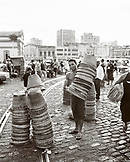Brazil, Belem, South America, basket vendor holding stack of baskets with buildings in the background
