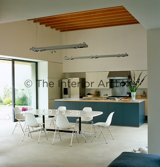 An Eames table and chairs in the dining area of this contemporary kitchen were originally designed for office use