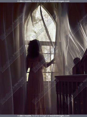 Woman in a long dress standing by a window with flying in the wind curtains in a dark house lit by dim sunlight