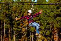 A woman (model) enjoys the zip line sports at the US National Whitewater Center in Charlotte, NC. The USNWC, an ultimate adventure playground for outdoor enthusiasts, offers both water and land sports.