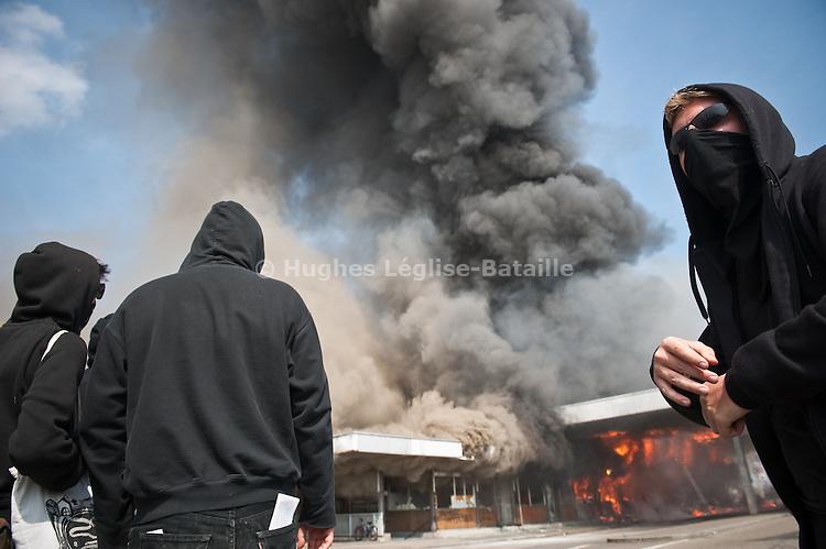 """Pres du Pont de l'Europe a Strasbourg, des membres du """"Black Block"""" regardent bruler l'ancien bureau des douanes durant la manifestation du 4 avril 2009 contre le sommet de l'OTAN..Credit;Hughes Leglise-Bataille/Julien Muguet/face to face"""