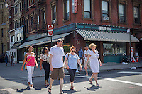 Pedestrians pass the Harlem Shake restaurant on Lenox Avenue in the neighborhood of Harlem in New York on Sunday, June 23, 2013. Wide sidewalks and a renaissance in Harlem have caused a number of restaurants to open catering to the more upwardly mobile newer residents. (© Frances M. Roberts)