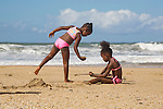 Two girls in pink playing with sand on Blanchisseuse beach