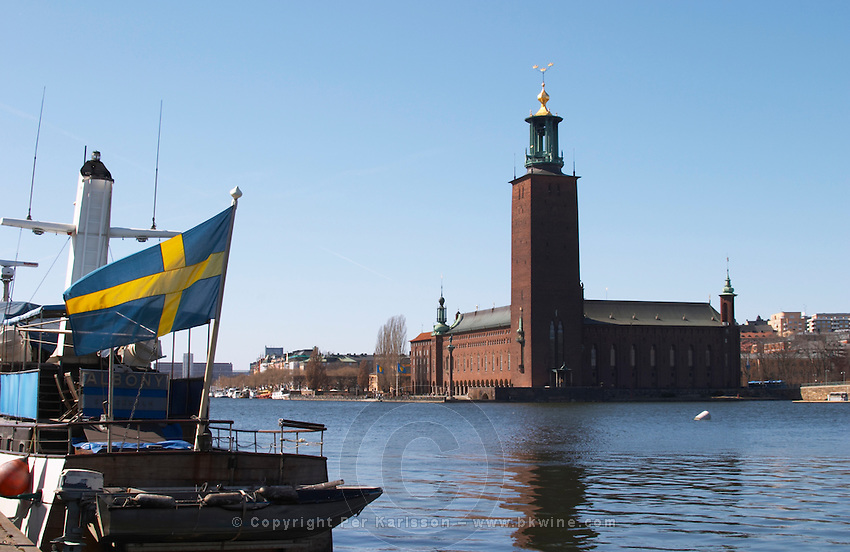 View to Stadshuset, the City Hall, over the Riddarfjarden, with its iconic tower with three crowns. A boat with a Swedish flag in the foreground. Kungsholmen Stockholm. Sweden, Europe.