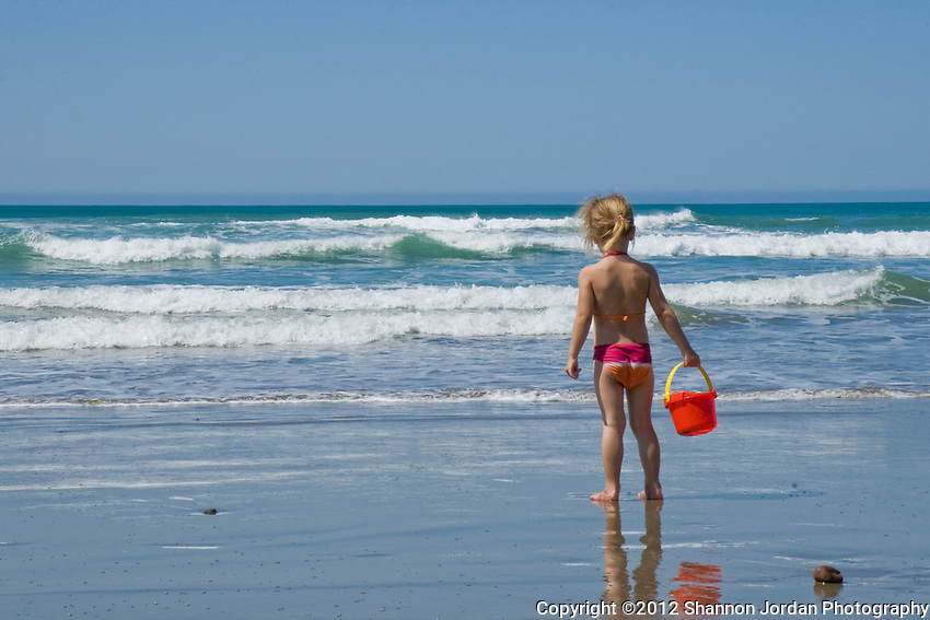 A little girl and her reflection contemplates her next move while building sandcastles and playing on the beach with her red bucket in Cayucos, California.
