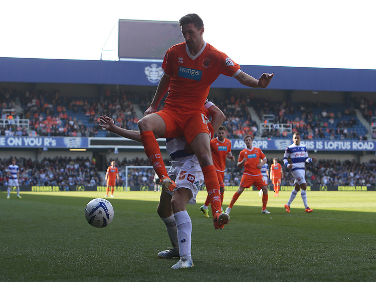 Blackpool's Chris Basham despite the attentions of  Queens Park Rangers' Nedum Onuoha<br /> <br /> Photo by Kieran Galvin/CameraSport<br /> <br /> Football - The Football League Sky Bet Championship - Queens Park Rangers v Blackpool - Saturday 29th March 2014 - Loftus Road - London<br /> <br /> &copy; CameraSport - 43 Linden Ave. Countesthorpe. Leicester. England. LE8 5PG - Tel: +44 (0) 116 277 4147 - admin@camerasport.com - www.camerasport.com