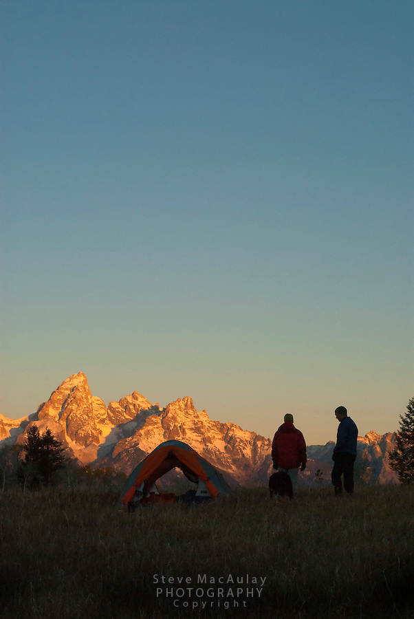 Sunrise on the Grand Tetons, as a couple with their dog stand next to tent, Grand Teton National Park, Jackson, Wyoming