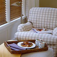 Tea and pastries served on a wicker tray in a corner of the bedroom