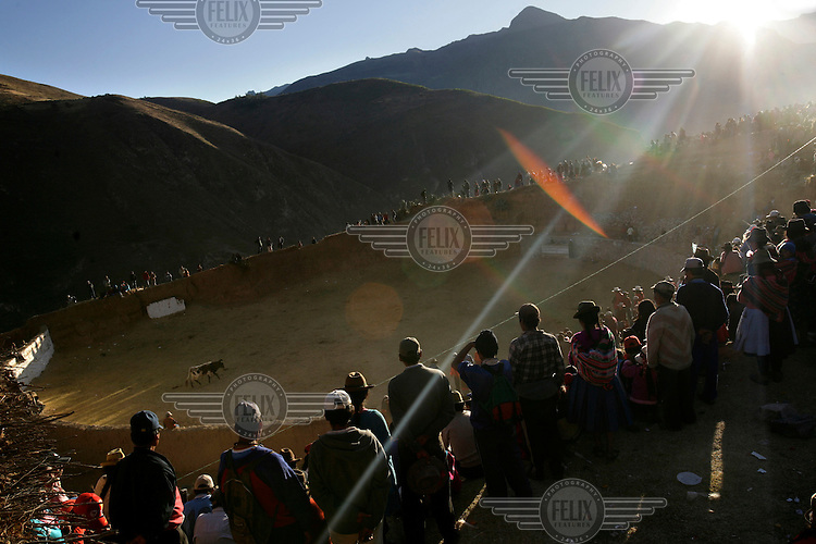 People look into a bullring to watch festivities at the Yawar Fiesta in Coyllurqui in the Peruvian Andes on Independence Day. This celebration symbolises the clash between the indigenous people (represented by a condor) and the Spanish (represented by a bull). The condor is paraded around town, strapped on top of the bull, given alcohol, and finally set free.
