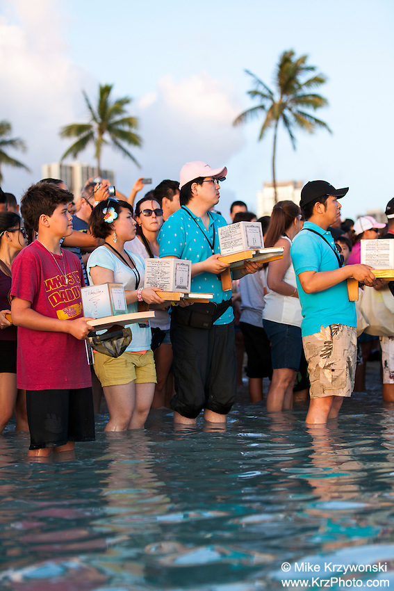 Participants standing in the water holding lanterns at the 15th annual Lantern Floating Ceremony at Ala Moana Beach Park on Memorial Day