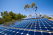 Workers install a solar array on a hillside in Malibu, Installation by Martifer Solar USA, California, USA