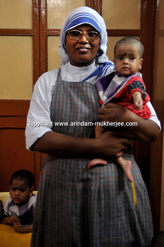 A sister holding a malnutrished child at Sishu Bhavan, which is the house for children founded by Mother Teresa.  Kolkata, West Bengal, India. 18th August 2010. Arindam Mukherjee