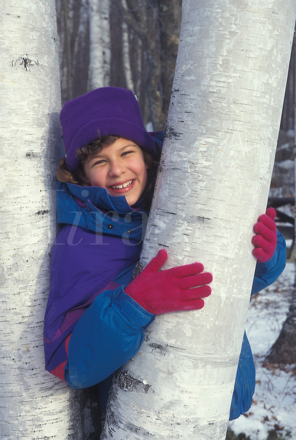 AJ4618, girl, Vermont, Birch tree, Girl (10 years old) smiles while posing for picture holding onto the white trunk of a birch tree in Groton State Forest in Caledonia County in the state of Vermont.