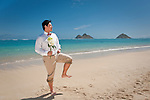 Asian groom goofs around with a Captain Morgan pose while waiting for his bride with a bouquet of flowers. Husband poses during a stroll on Lanikai beach as they look forward to their life as a married couple following their wedding.