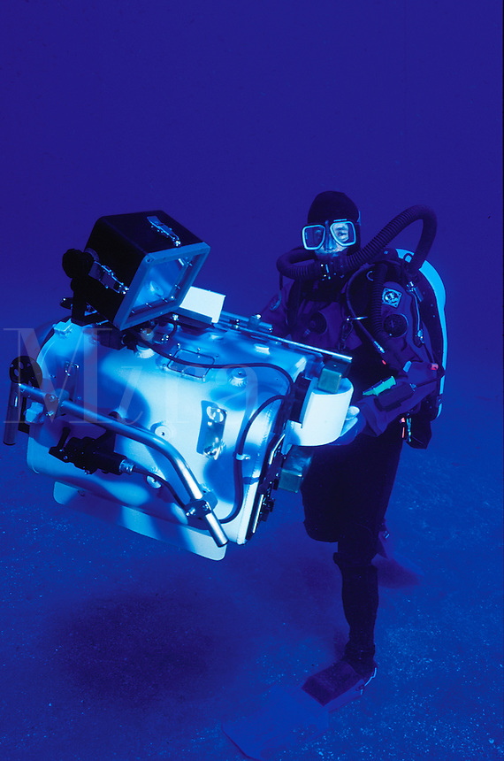 Diver wearing closed-circuit rebreather holding IMAX underwater camera housing.Coronado s Islands, Mexico.