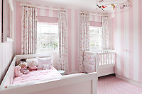 A pink striped child's bedroom with curtains patterned with carousel horses and a delicate ceiling light with colourful birds