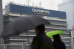 November 11, 2011, Tokyo, Japan - Against the backdrop of Olympus billboard, pedestrians scurry by in the cold mid-autumn rain in Tokyos Shinjuku on Friday, November 11, 2011. As is the weather, bleak is the companys future. The admission of the worlds biggest maker of endoscopes that it has hidden securities losses may lead to its delisting by the Tokyo Stock Exchange as Japanese police have reportedly launched a full investigation into the companys concealment dating back to the 1980s. Olympus said its likely to miss November 14 deadline for releasing its first-half earnings, prompting the TSE to place the Tokyo-based company on a watch list for a review for possible delisting. Olympus shares have lost around 80 per cent of their value since the scandal broke on October 14 when the company ousted British CEO Michael Woodford, who alleged overpayments in the acquisition deals. (Photo by Yutaka/AFLO) [1040] -mis-