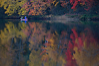 A couple paddles a canoe through fall color reflected in Harlow Lake near Marquette Michigan in autumn.