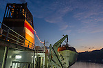 A colorful PELNI ship smoke stack and life boat against an evening sky.