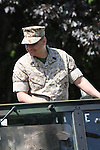 A male US Marines soldier riding a jeep standing and smiling