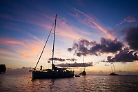 Man coiling line aboard cruising yacht at sunset