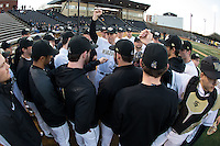 Wake Forest Demon Deacons head coach Tom Walter (center) huddles with his team prior to the start of the game against the Georgetown Hoyas at David F. Couch Ballpark on February 19, 2016 in Winston-Salem, North Carolina.  The Demon Deacons defeated the Hoyas 3-1.  (Brian Westerholt/Four Seam Images)