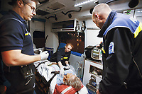 Switzerland. Canton Ticino. Lugano. A senior woman is brought by ambulance to hospital for medical examinations. The elderly man is suffering from a stroke. The emergency doctor Daniele Speciale (L) is working with two paramedics. They all work for the Croce Verde Lugano. They wear blue uniforms and medical gloves. The man (R) is a professional certified nurse, the woman (C) is a volunteer specifically trained in emergency rescue. A monitor controls the patient's vital functions, such as electrocardiogram, blood pressure's measurement, respiratory rate and pulse oximetry (oxygen saturation). On the aged woman's arm, an intravenous infusion with saline solution is fixed. The Croce Verde Lugano is a private organization which ensure health safety by addressing different emergencies services and rescue services. Volunteering is generally considered an altruistic activity where an individual provides services for no financial or social gain to benefit another person, group or organization. Volunteering is also renowned for skill development and is often intended to promote goodness or to improve human quality of life. Medical gloves are made of different polymers including latex, nitrile rubber, polyvinyl chloride and neoprene. 13.01.2018 © 2018 Didier Ruef