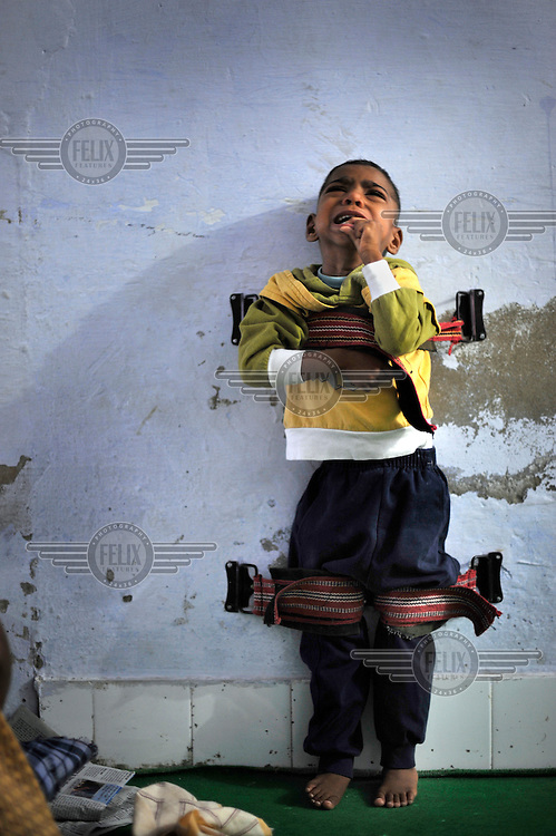 4 year old Akriti who has cerebral palsy cries as he is strapped to a wall to help straighten his limbs at the privately funded Baba Farid Centre in Faridkot. An increasing and ignored percentage of children are being born suffering the side effects of industrial pollution. The Baba Farid Centre was set up by Dr Pritpal Singh and is staffed on a volunteer basis by his network of similarly concerned fellow junior doctors and specialists. It treats its patients with a mixture of homeopathic, ayurvedic and acupuncture methods.