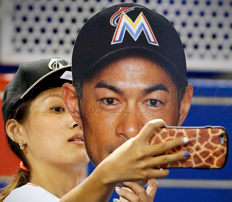 A fan of Miami Marlins right fielder Ichiro Suzuki (51) holds an over seized photo of him as she takes a selfie as the Florida Marlins play host to the New York Mets on Friday, July 22, 2016.