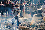 A woman walks through ash from the ceremonial fire during the Fire-walking Festival (Hiwatari-sai) at Mt. Takao on Sunday, March 12, 2017 in Hachioji, Japan.<br /> Photo by Kevin Clifford