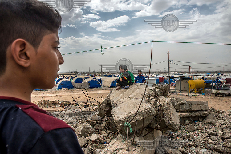 Children play on the rubble of a destroyed house in Hajj Ali IDP camp, home to thousands of people displaced by ISIS.