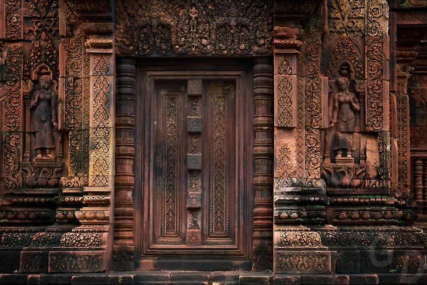 Banteay Srei during the wet season glowing in the last light of the afternoon.The temple of Banteay Srei or the Citadel of the Women.<br /> <br /> The special charm of this temple lies in its remarkable state of preservation, small size and excellence of decoration.<br /> The unanimous opinion amongst French archaeologists who worked at Angkor is that Banteay Srei is a 'precious gem' and a 'jewel in Khmer art'. Banteay Srei, as it is known by locals, was originally called Isvarapura, according to inscriptions. It was by a Brahmin of royal descent who was spiritual teacher to Jayavarman V. Some describe it a s being closer in architecture and decoration to Indian models than any other temple at Angkor. A special feature of the exquisite decoration was the use of a hard pink sandstone (quartz arenite) where enabled the 'technique of sandalwood carving with even an Indian scent to it'.