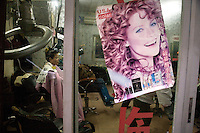 A woman sits in a hair salon getting her hair done in Haikou, Hainan, China.