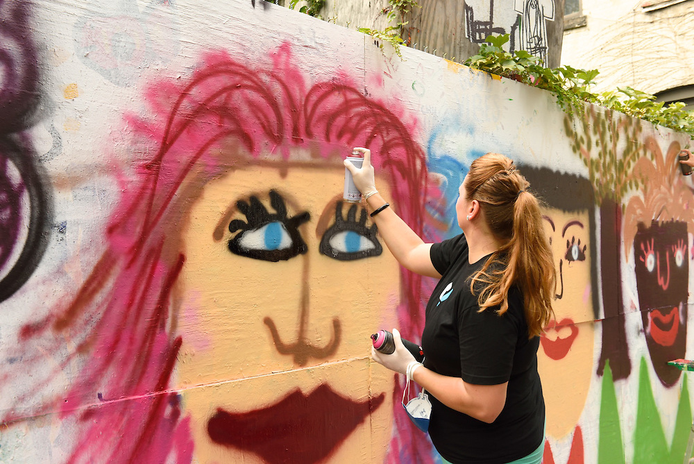 Spray painting a face with pink hair.
