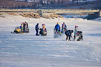 Volunteers chop holes in ice to put in wood stake trail markers on Unalakleet near Unalakleet