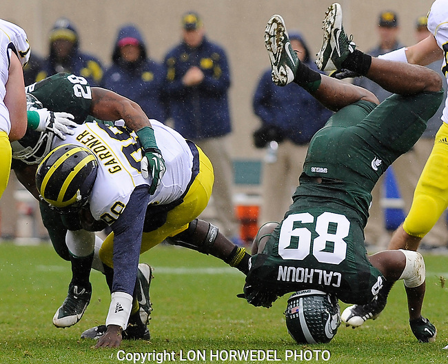 November 2, 2013: Michigan quarterback Devin Gardner gets sacked by Michigan State's Denicos Allen as Allen's teammate Shilique Calhoun just misses Gardner while diving over the pile during first quarter action of MSU's 29-6 win over Michigan, Saturday at Spartan Stadium in East Lansing.
