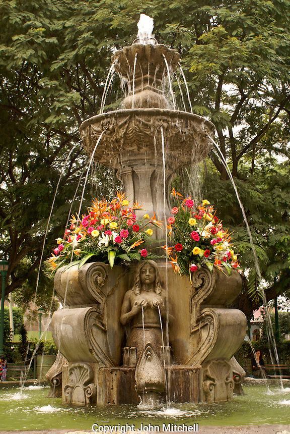 Flower bedecked fountain in the Parque Central, Antigua, Guatemala. Antigua is a UNESCO World heritage site...