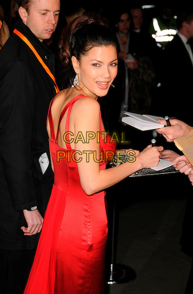 NATASSIA SCARLET MALTHE.The Orange British Academy Film Awards 2008, aftershow party, Grosvenor House Hotel, London, England.  .February 10th, 2008 .BAFTA Arts half length red dress looking over shoulder signing autographs .CAP/CAN.©Can Nguyen/Capital Pictures